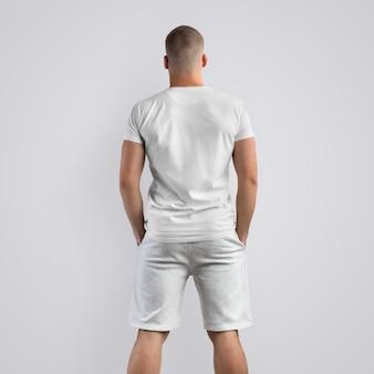 Homem jovem musculoso caucasiano em uma camiseta em branco e shorts cinza de malha em um fundo branco do estúdio. pose de costas. o modelo pode ser usado em seu design.
