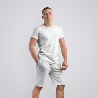Homem jovem musculoso caucasiano em uma camiseta em branco e shorts cinza de malha em um fundo branco do estúdio. pose frontal. o modelo pode ser usado em seu design.