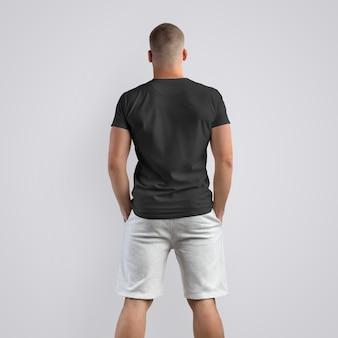 Homem jovem musculoso caucasiano em uma camiseta preta e shorts cinza de malha em um fundo branco do estúdio. pose de costas. o modelo pode ser usado em seu design.