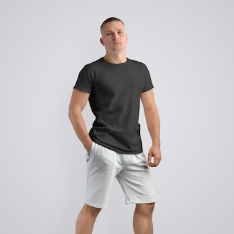 Homem jovem musculoso caucasiano em uma camiseta preta e shorts cinza de malha em um fundo branco do estúdio. pose frontal. o modelo pode ser usado em seu design.