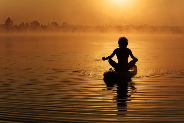 Homem jovem musculoso em silhueta meditando na prancha de remo durante o belo nascer do sol acima do lago.