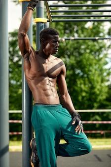 Homem jovem musculoso exercitando-se no campo de esportes. homem africano olhando para o lado enquanto faz exercícios de barra horizontal. modelo masculino sem camisa, exercitando ao ar livre.