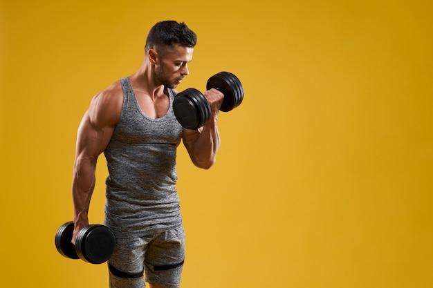 Homem jovem musculoso fazendo exercício com halteres