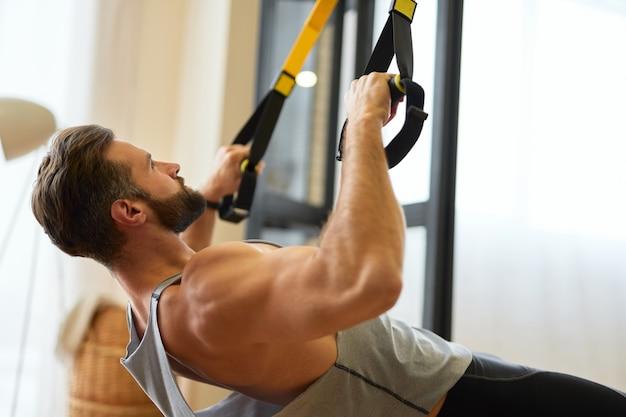 Homem jovem musculoso fazendo exercícios com faixa elástica de fitness