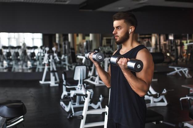 Homem jovem musculoso malhando na academia, fazendo exercícios com halteres no bíceps