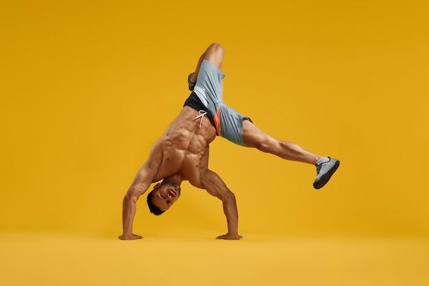 Homem jovem musculoso realizando acrobacia de cabeça pra baixo