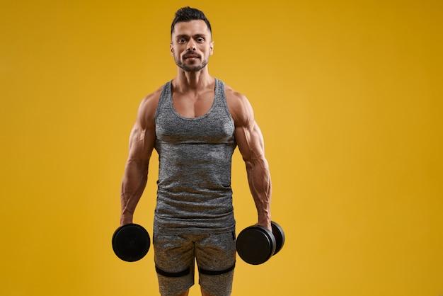 Homem jovem musculoso segurando halteres