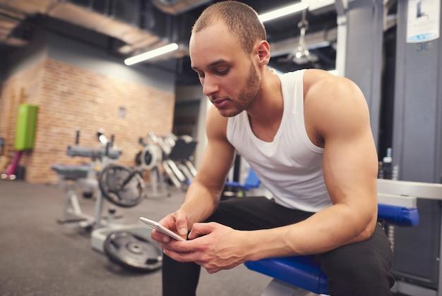 Homem jovem musculoso usando telefone celular na academia