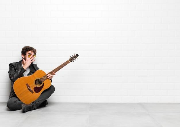 Homem jovem músico se sentindo assustado ou envergonhado, espiando ou espionando com os olhos semicobertos com as mãos com um violão