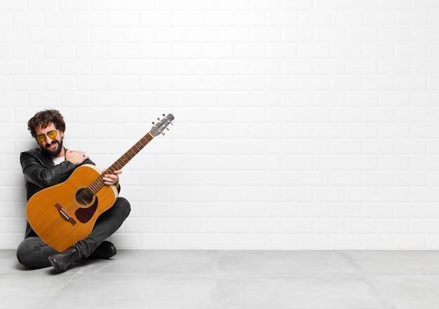 Homem jovem músico, sentindo-se ansioso, doente, doente e infeliz, sofrendo uma dor de estômago dolorosa ou gripe com um conceito de guitarra, rock and roll