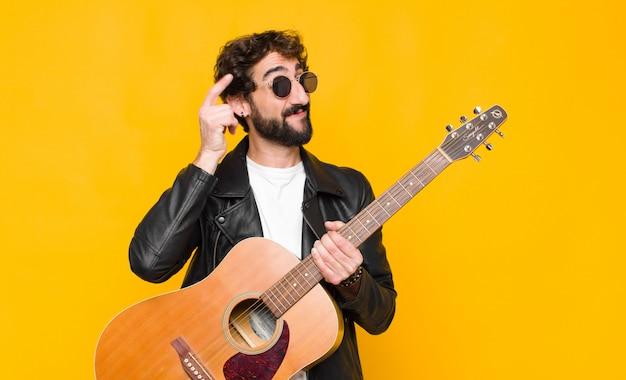Homem jovem músico sorrindo alegremente e apontando enquanto faz um gesto depois de ligar para você, falando ao telefone com uma guitarra, conceito de rock and roll