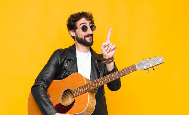 Homem jovem músico sorrindo com orgulho e confiança, fazendo a pose número um triunfante, sentindo-se como um líder com uma guitarra