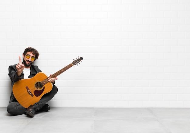 Homem jovem músico sorrindo e olhando amigável, mostrando o número um ou primeiro com a mão para a frente, contando com um conceito de guitarra, rock and roll