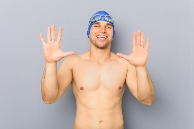 Homem jovem nadador profissional mostrando o número dez com as mãos.