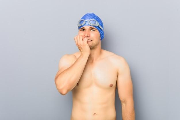 Homem jovem nadador profissional, roer unhas, nervoso e muito ansioso.
