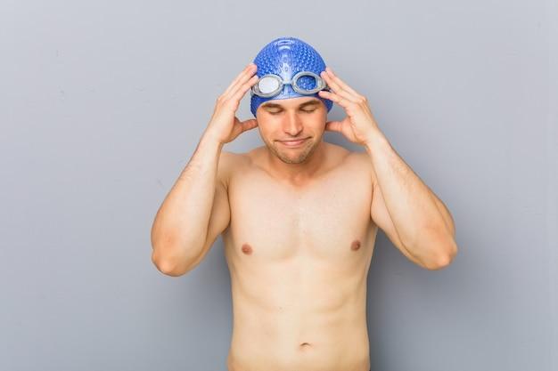 Homem jovem nadador profissional tocando os templos e tendo dor de cabeça.