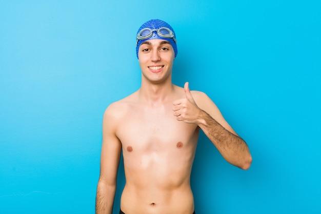 Homem jovem nadador sorrindo e levantando o polegar