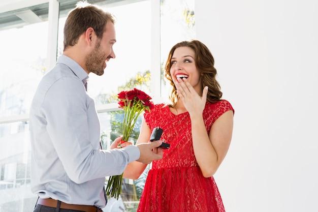 Homem jovem, oferecendo, flores, e, anel acoplamento, para, bonito, mulher