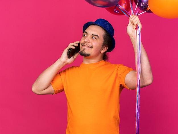 Homem jovem olhando para o lado satisfeito com um chapéu de festa segurando balões e falando no telefone isolado na parede rosa