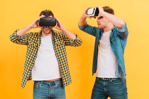 Homem jovem, olhar, seu, amigo, desfrutando, a, realidade virtual, óculos, contra, amarela, fundo
