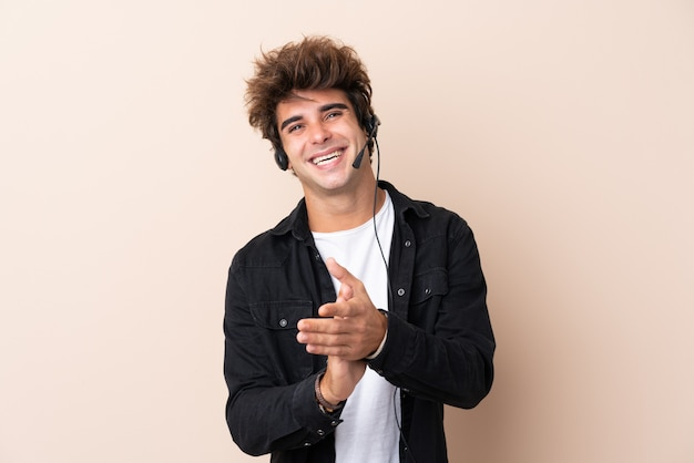 Homem jovem operador de telemarketing sobre parede isolada