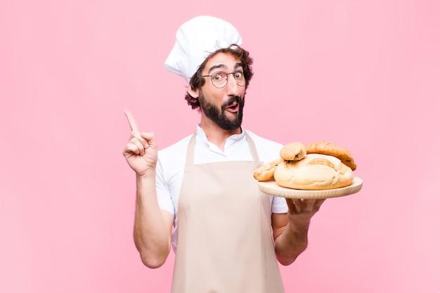 Homem jovem padeiro louco segurando o pão contra a parede rosa
