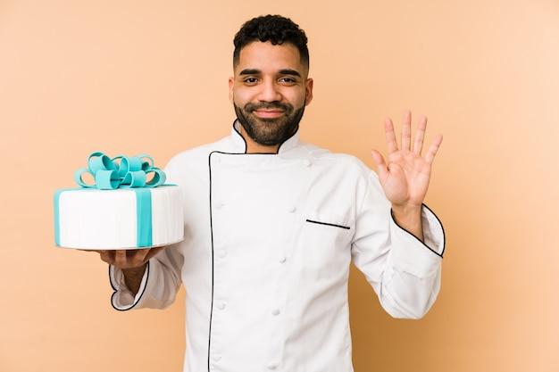Homem jovem padeiro segurando um bolo isolado sorrindo alegre mostrando o número cinco com os dedos
