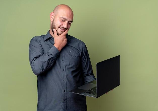 Homem jovem pensativo careca de call center segurando e olhando para um laptop, colocando a mão no queixo isolado na parede verde oliva