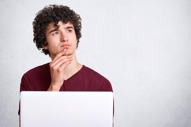 Homem jovem pensativo com cabelo encaracolado, mantém o queixo e olha pensativamente de lado