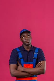 Homem jovem pensativo construtor afro-americano usando uniforme de construção e boné em pé com os braços cruzados no peito, olhando para cima em pé na rosa