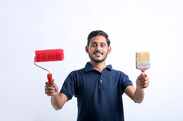 Homem jovem pintor indiano sobre fundo branco.