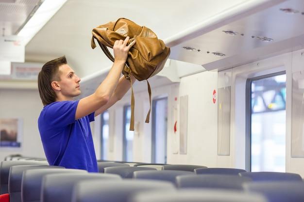 Homem jovem, pôr, bagagem, em, despesas gerais, locker, em, trem