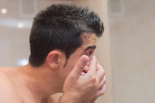 Homem jovem, pôr, lente contato, em, seu, olho