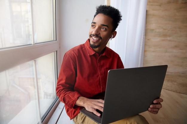 Homem jovem positivo, barbudo, de cabelos curtos, morena, com pele escura, mantendo o laptop sobre os joelhos enquanto está sentado no parapeito da janela e olhando alegremente para fora da janela