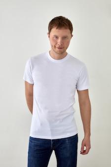 Homem jovem positivo em jeans com a mão atrás e camiseta branca em pé