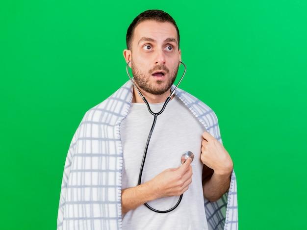 Homem jovem preocupado, usando e ouvindo seus próprios batimentos cardíacos com um estetoscópio isolado sobre fundo verde