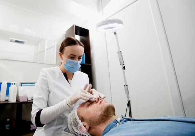 Homem jovem preparando sua pele com uma massagem na pele relaxada. resolver alguns problemas de pele relacionados com a idade e torná-la macia e saudável.