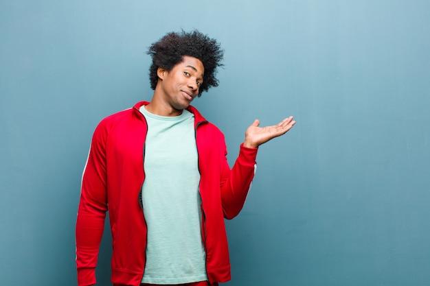 Homem jovem preto esportes se sentindo feliz e sorrindo casualmente, olhando para um objeto ou conceito realizado na mão do lado