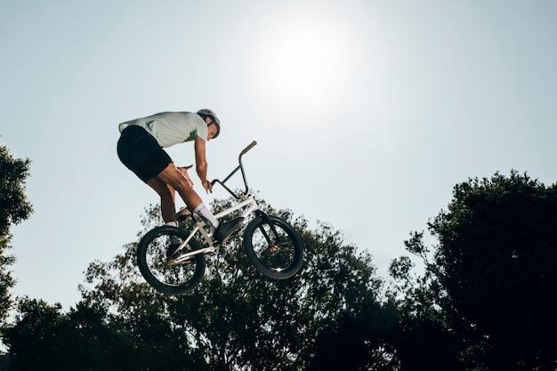 Homem jovem, pular bicicleta, alto