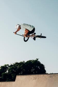 Homem jovem, pular, com, bicicleta bmx, vista baixa ângulo