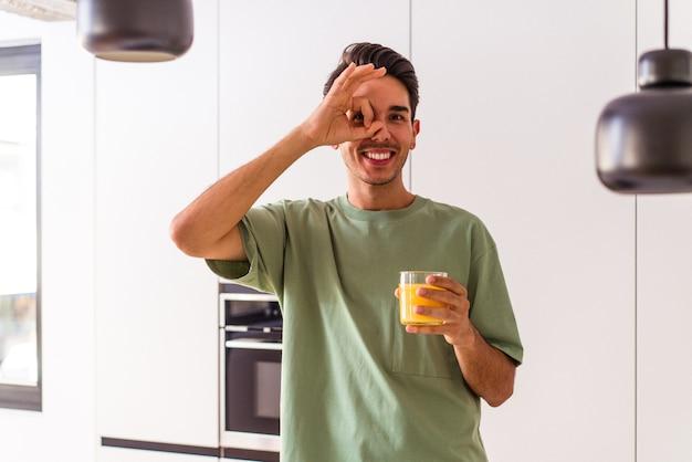 Homem jovem raça mista bebendo suco de laranja em sua cozinha animado, mantendo o gesto ok no olho.