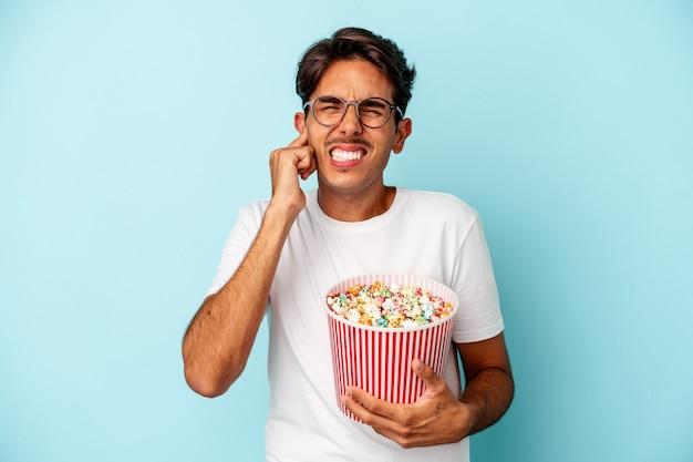 Homem jovem raça mista comendo pipocas isoladas em fundo azul, cobrindo as orelhas com as mãos.