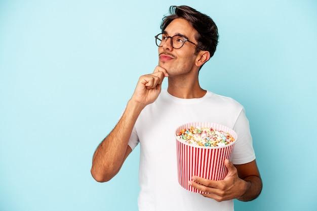 Homem jovem raça mista comendo pipocas isoladas em fundo azul, olhando de soslaio com expressão duvidosa e cética.