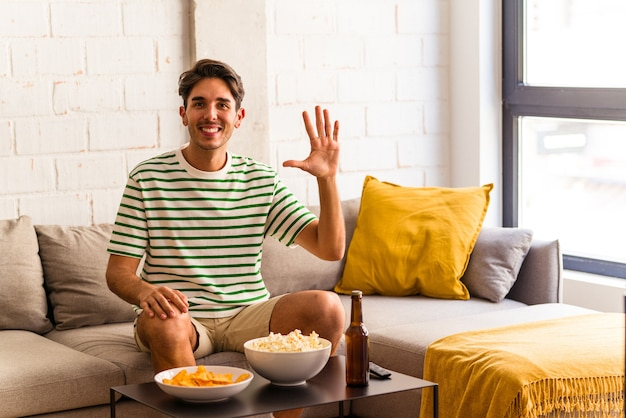Homem jovem raça mista comendo pipocas, sentado no sofá, sorrindo alegre mostrando o número cinco com os dedos.