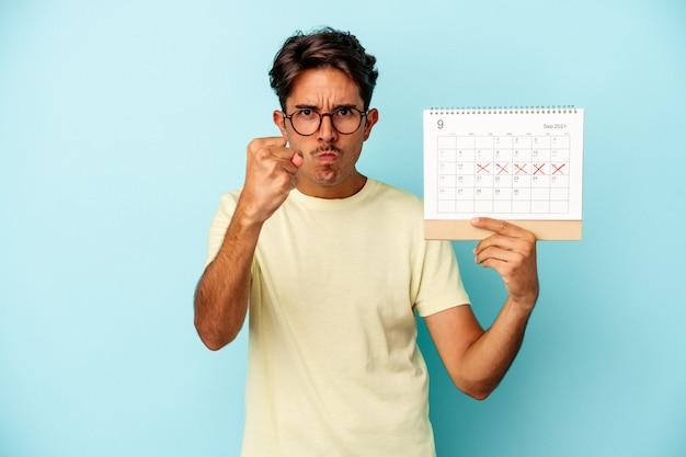 Homem jovem raça mista segurando calendário isolado em fundo azul, mostrando o punho para a câmera, expressão facial agressiva.