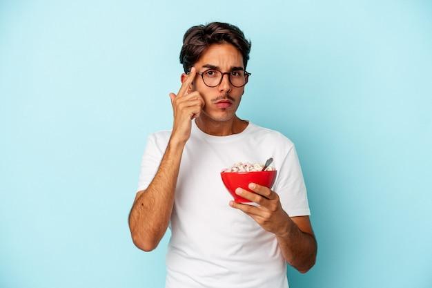 Homem jovem raça mista segurando cereais isolados no templo apontando de fundo azul com o dedo, pensando, focado em uma tarefa.