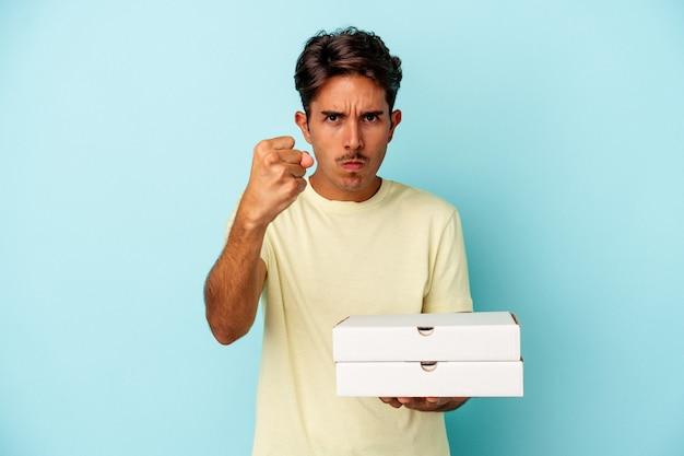 Homem jovem raça mista segurando pizzas isoladas em fundo azul, mostrando o punho para a câmera, expressão facial agressiva.