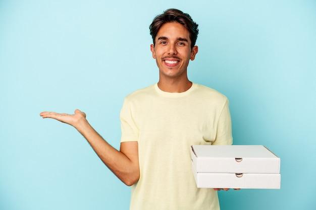 Homem jovem raça mista segurando pizzas isoladas em fundo azul, mostrando um espaço de cópia na palma da mão e segurando a outra mão na cintura.