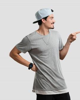 Homem jovem rapper apontando para o lado, sorrindo surpreso apresentando algo, natural e casual