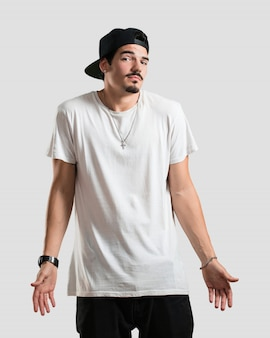 Homem jovem rapper duvidando e encolhendo os ombros, conceito de indecisão e insegurança, incerto sobre algo